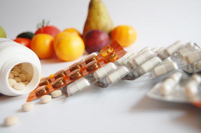 různé léky s ovocem v pozadí
