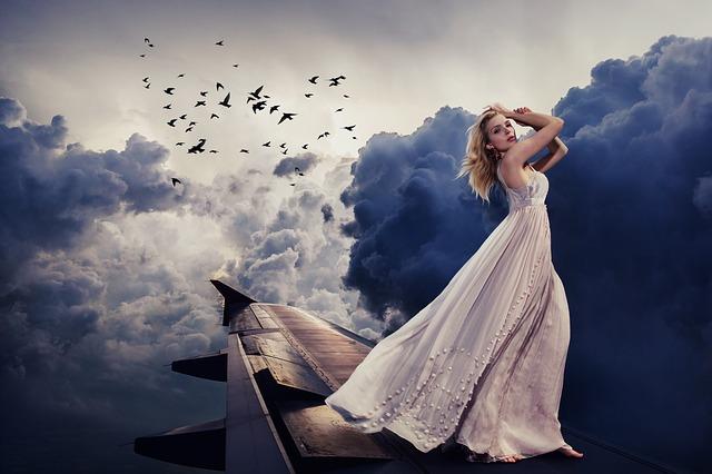 žena ve večerních šatech v oblacích